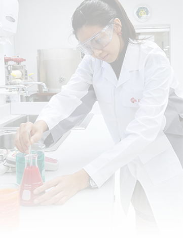 female scientist in lab coat wearing goggles removing red sample from flask
